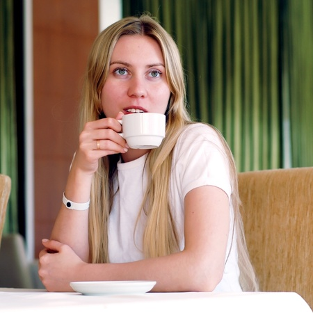 Happy woman in white with cup of coffee or tea. photo