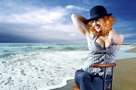 Young woman in black hat seating on the beach Stock Photo - 9265690
