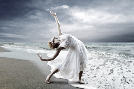 Woman dancer posing on the beach Stock Photo