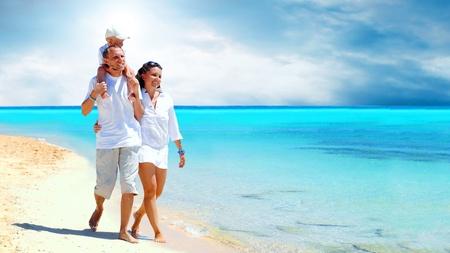 child bikini: View of happy young family having fun on the beach
