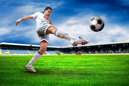 futbolista: Jugador de fútbol de felicidad después de gol en el campo del estadio con cielo azul