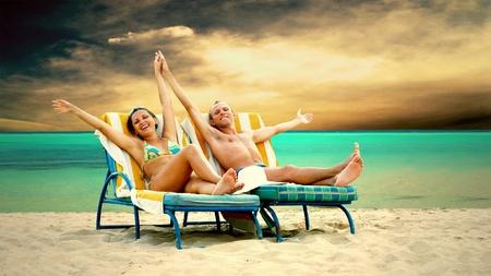 strandstoel: Achteraanzicht van een paar op een ligstoel ontspannen op het strand