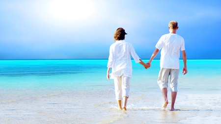 séta: Rear view of a couple walking on the beach, holding hands.