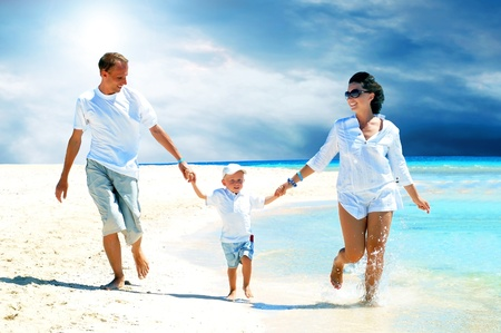 View of happy young family having fun on the beach Stock Photo - 9514215