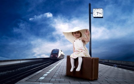 Little girl sitting on vintage baggage on the train platform of railway station Stock Photo - 9648763