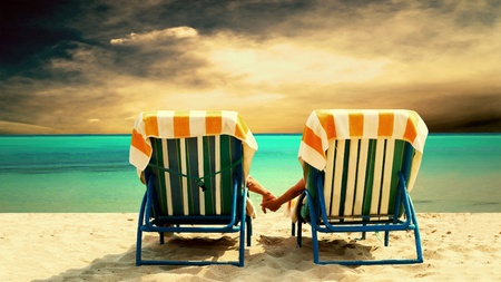 Rear view of a couple on a deck chair relaxing on the beach Stock Photo - 9648786