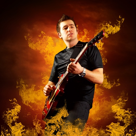 Rock guitarist play on the electric guitar around fire flames photo