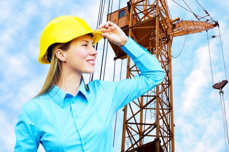 building worker: Young architect-woman wearing a protective helmet standing on the building background