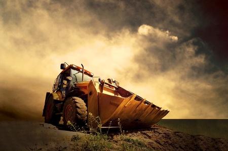 Gelbe Traktor auf goldenen Sonnenaufgang Himmel