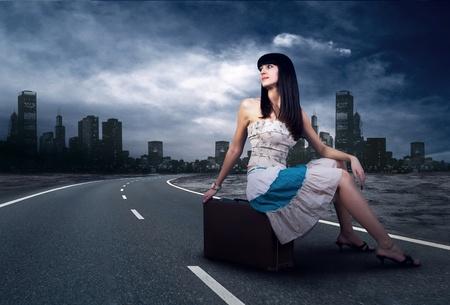 mujer hippie: Joven esperando en el camino con su equipaje vintage Foto de archivo