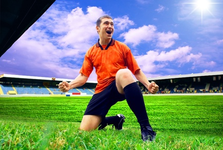 Happiness football player after goal on the field of stadium with blue sky Stock Photo - 9851037
