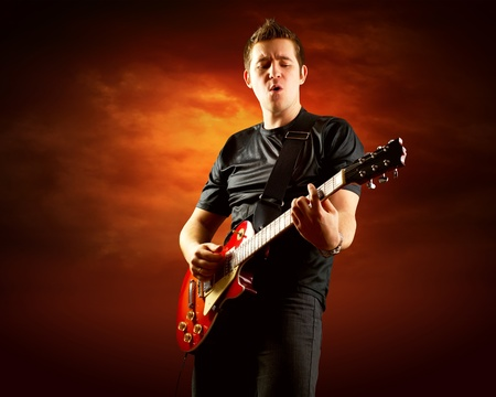 Rock guitarist play on the electric guitar around fire flames Stock Photo - 9850946