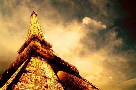 vintage paris: PARIS - JUNE 22 : Illuminated Eiffel tower at night sky June 22, 2010 in Paris. The Eiffel tower is one of the most recognizable landmarks in the world.