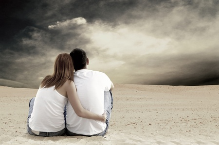 Young couple seating in desert in sunny day photo