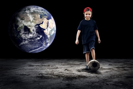 Child football player and Grunge ball on the dark background photo