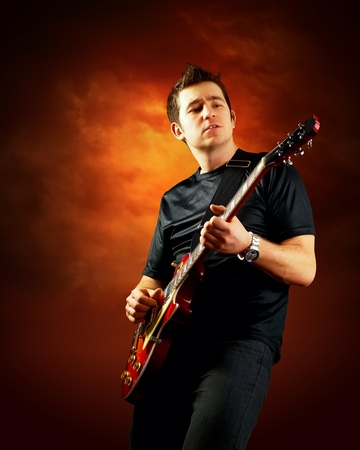 Rock guitarist play on the electric guitar, orange sky background photo