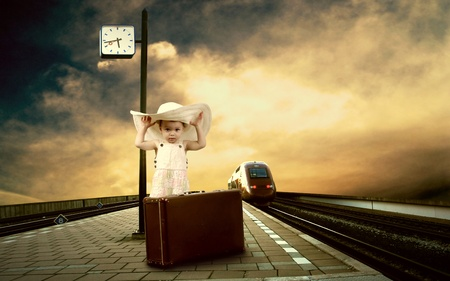 baggage train: Little girl sitting on vintage baggage on the train platform of railway station