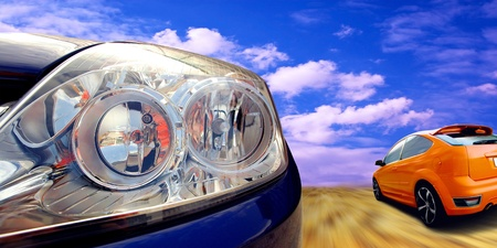 motor vehicle: Headlight of blue car on sky with clouds background
