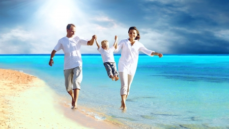 View of happy young family having fun on the beach Stock Photo - 10049451