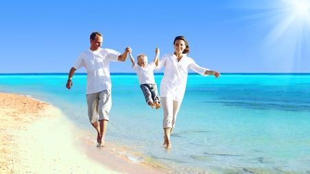 familia viaje: Vista de la joven familia feliz que se divierte en la playa