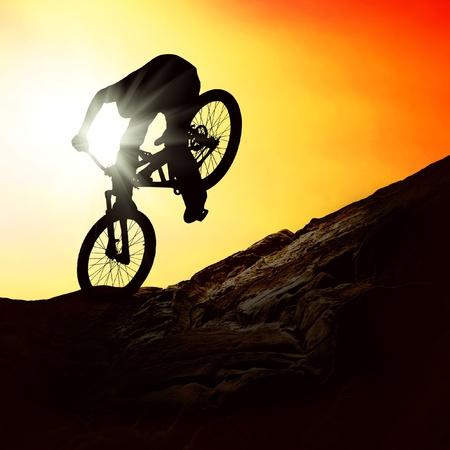mountain biker: Silhouette of a man on muontain-bike, sunset Stock Photo