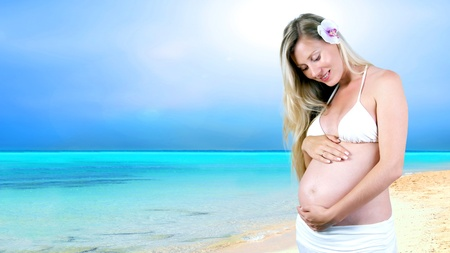 Happiness pregnant women in the white on the sunny tropical beach photo