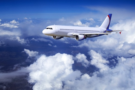 Airplane at fly on the sky with clouds Stock Photo - 10344563