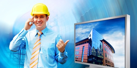 construction plan: Young architect wearing a protective helmet standing on the building background Stock Photo