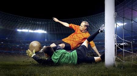 arquero futbol: Jugador de fútbol y el salto del portero en el campo del estadio en la noche