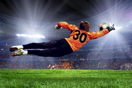 Football goalman on the stadium field Фото со стока