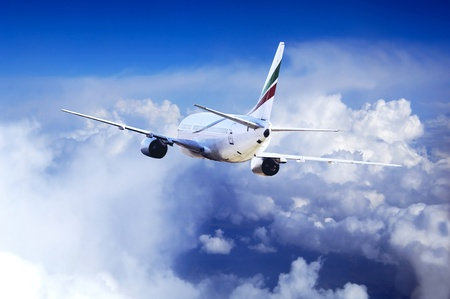 Airplane at fly on the sky with clouds Stock Photo - 10492485