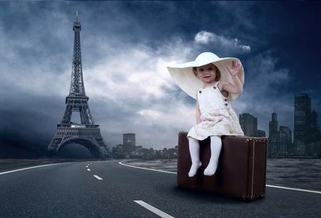 paris vintage: Niña esperando en la carretera con su equipaje vintage Foto de archivo
