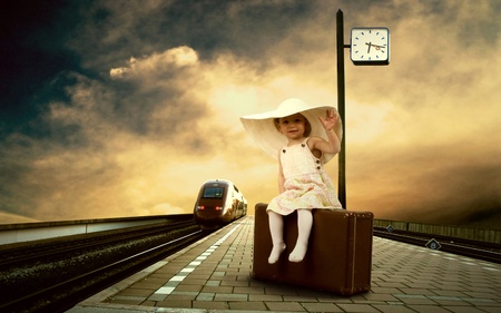 Little girl sitting on vintage baggage on the train platform of railway station photo