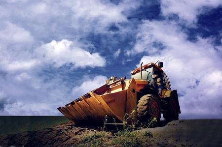 gold shovel: Yellow tractor on golden sunrise sky