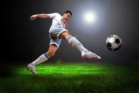 La felicidad jugador de fútbol tras el gol en el campo del estadio con la luz