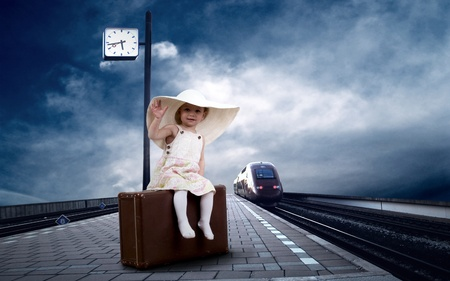 childchood: Little girl sitting on vintage baggage on the train platform of railway station