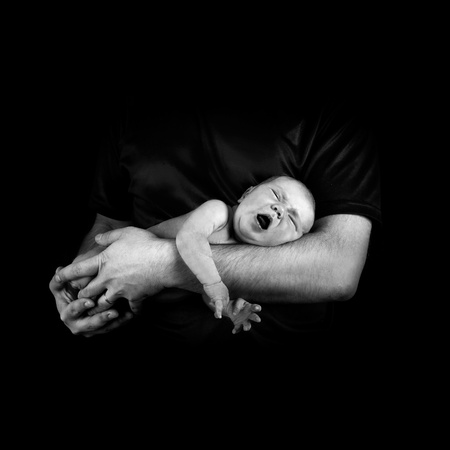 Newborn baby on the fathers hands photo