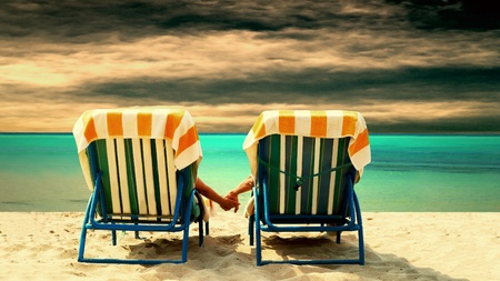 couples outdoors: Rear view of a couple on a deck chair relaxing on the beach