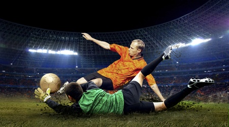 football players: Football player and jump of goalkeeper on the field of stadium at night