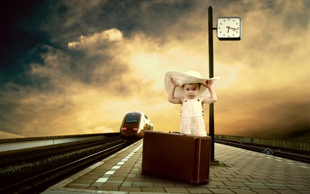 Little girl sitting on vintage baggage on the train platform of railway station photo