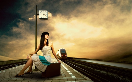 Girl waiting train on the platform of railway station photo