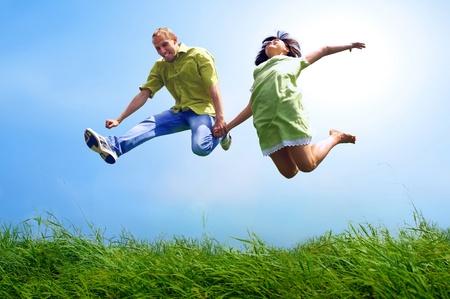 Diversión pareja en salto en el fondo al aire libre