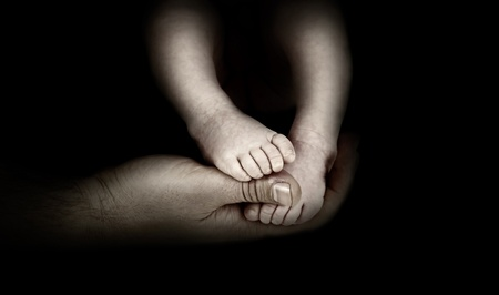 the infancy: Babys foots in father hands on the monochrome background