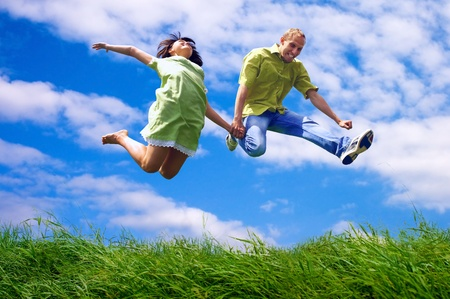Fun couple in jump on the outdoor background Stock Photo - 12973306
