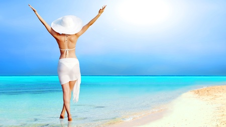 carefree: Young beautiful women in the white on the sunny tropical beach Stock Photo