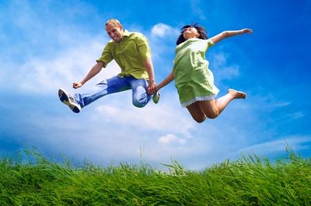pareja saludable: Diversión pareja en salto en el fondo al aire libre