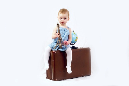 A little girl with globe and old baggage Stock Photo - 13568479