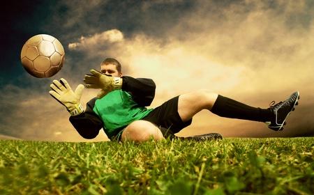 Jump of football goalman on the outdoor field photo