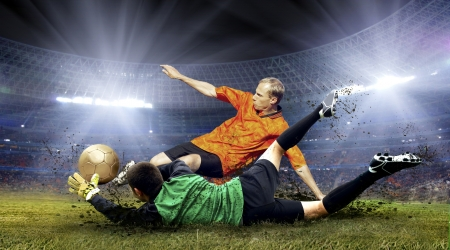 Football player and jump of goalkeeper on the field of stadium at night photo