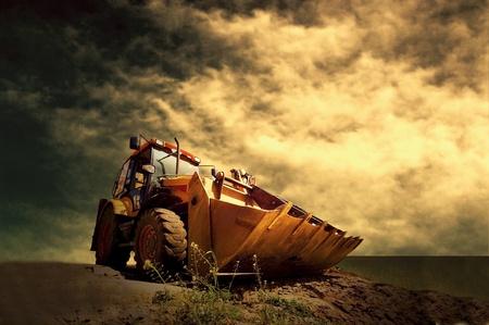 bulldozers: Yellow tractor on golden sunrise sky